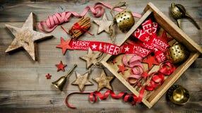 Rojo y decoraciones de la Navidad del oro en fondo de madera Fotos de archivo