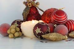 Rojo y decoraciones de la Navidad del oro y vela ardiente Imagen de archivo