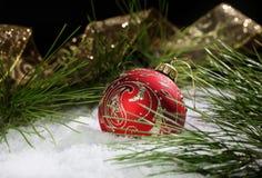 Rojo y ornamento de la Navidad del oro en nieve fotos de archivo