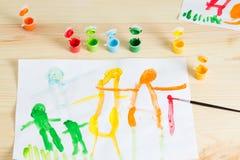 3 rok dzieciaki rysuje szczęśliwego rodzinnego obrazek na drewnianym stole  Obraz Stock