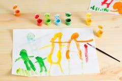 3 rok dzieciaki rysuje szczęśliwego rodzinnego obrazek na drewnianym stole  Obrazy Stock