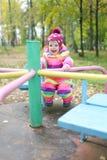 1 rok małej dziewczynki jazdy na carousel w jesieni outdoors Obrazy Royalty Free