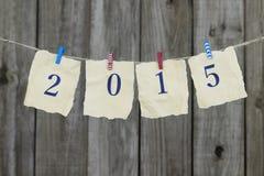 Rok 2015 na antykwarskim papierowym obwieszeniu czerwieni, białych i błękitnych clothespins na clothesline drewnem, ono fechtuje  Fotografia Stock