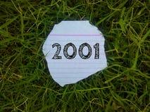 Rok 2001 pisać na kawałek papieru w trawie fotografia stock