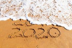 2020 rok rysujących na piasku myje daleko od falą obraz stock