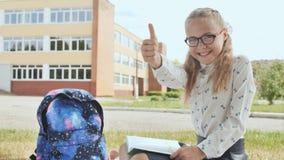 Rok uczennica z książką siedzi na trawie i pokazuje palec wewnątrz up dobry humor zdjęcie wideo
