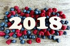 Rok 2018 z czarnymi jagodami i malinkami na drewnianym backgroun Fotografia Stock