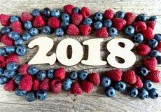 Rok 2018 z czarnymi jagodami i malinkami na drewnianym backgroun Fotografia Royalty Free