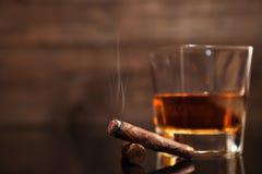 Rokend sigaar en glas whisky op de achtergrond Royalty-vrije Stock Fotografie
