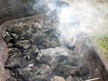 Rokende brandende houtskool op barbecue Stock Afbeeldingen