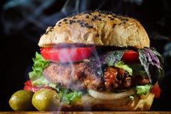 Rokende hete grote sappige Hamburger Stock Afbeeldingen