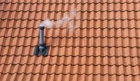 Rokende schoorsteen op dak Stock Foto's