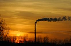 Rokende schoorsteen van een fabriek in de zonsondergang stock foto's