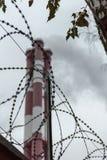 Rokende schoorstenen achter een omheining stock fotografie