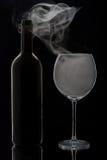 Rokende wijnglas en fles Stock Foto