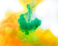 rokerige achtergrond met groene en oranje verf die in water stromen royalty-vrije stock afbeeldingen