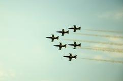 Rokerige acrobatische jets op kleurrijke hemel Stock Afbeelding