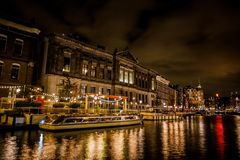 Rokin Amsterdam Boats at Night. Rokin is a canal and major street in Amsterdam, the Netherlands. Originally it was part of the river Amstel, and was known then Royalty Free Stock Image
