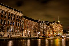 Rokin Amsterdam Boats at Night. Rokin is a canal and major street in Amsterdam, the Netherlands. Originally it was part of the river Amstel, and was known then Stock Photo
