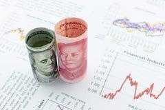 Rolado acima dos rolos da nota de dólar dos E.U. e do chinês Yuan com imagem/retrato do presidente Mao Zedong e Benjamin Franklin Imagens de Stock