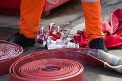 Rolado em uma mangueira de fogo vermelho do rolo, extintores r do equipamento do fogo imagem de stock