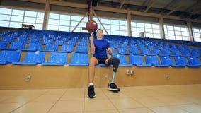 Rolamento da pessoa deficiente uma bola ao sentar-se em um campo de básquete, prótese biônico video estoque