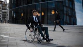 Rolamento deficiente do homem de negócios na cadeira de rodas perto do businesscentre video estoque