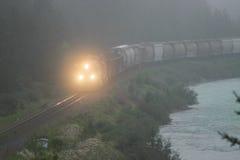 Rolamento do trem ao longo do rio na névoa Fotos de Stock Royalty Free