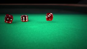 Rolamento vermelho de três dados na tabela de jogo do jogo verde no fundo preto, disparando com movimento lento, conceito da recr vídeos de arquivo