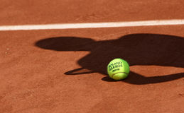 Roland Garros 2010 official ball. PARIS - MAY 20: Official ball of the French Open Grand Slam tennis tournament with the shadow of a tennis player on the clay Royalty Free Stock Photography