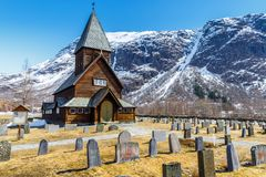 Roldal Stave Church Roldal stavkyrkje with snow cap mountain b Royalty Free Stock Photo