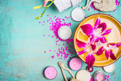 Role com água e as flores cor-de-rosa da orquídea com bem-estar e o ajuste dos termas no fundo do azul de turquesa Imagem de Stock