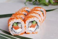 Role com laranja do tobiko, salmões, camarão do pepino e pimentas vermelhas doces em um menu tropical do close-up da folha isolad Fotos de Stock