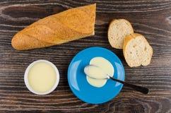 Role com leite condensado, colher, leite em uns pires azuis, pão fotos de stock