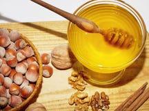 Role com mel e cesta com as avelã na tabela de madeira Imagem de Stock Royalty Free