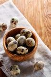 Role com ovos codorniz, ovos em um guardanapo homespun na tabela de madeira, close-up, foco seletivo Fotografia de Stock