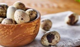 Role com ovos codorniz, ovos em um guardanapo homespun na tabela de madeira, close-up, foco seletivo Foto de Stock