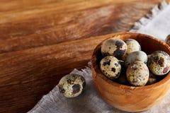 Role com ovos codorniz, ovos em um guardanapo homespun na tabela de madeira, close-up, foco seletivo Imagem de Stock Royalty Free
