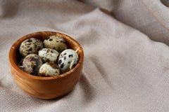 Role com ovos codorniz, ovos em um guardanapo homespun na tabela de madeira, close-up, foco seletivo Imagens de Stock