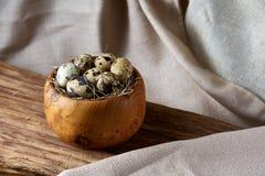 Role com ovos codorniz, ovos na parte de madeira em uma toalha de mesa homespun, close-up, foco seletivo Foto de Stock
