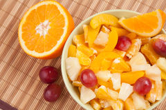 Role com salada de fruto com metade da laranja imagem de stock