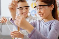Upbeat boy watching his classmate mix chemicals. Role model. Cheerful teenage boy in safety goggles watching her classmate mix chemicals in a test tube and Stock Image