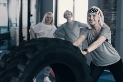 Personal trainer showing tire exercises to her clients. Role model. Pleasant senior female personal trainer showing a complex of workout exercises with a big Royalty Free Stock Photography