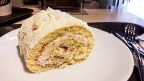 Role o bolo na placa branca com forquilha e na faca no café Imagens de Stock Royalty Free