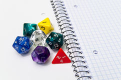 Role playing dices lying on exercise book Stock Photography