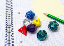 Role playing dices lying on exercise book Stock Images