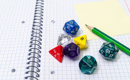 Role playing dices lying on exercise book Royalty Free Stock Images