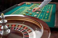 A roleta e as pilhas do jogo lascam-se em uma tabela verde Fotografia de Stock