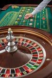 A roleta e as pilhas do jogo lascam-se em uma tabela verde Imagem de Stock Royalty Free