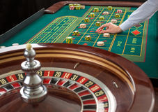 A roleta e as pilhas do jogo lascam-se em uma tabela verde Fotos de Stock Royalty Free